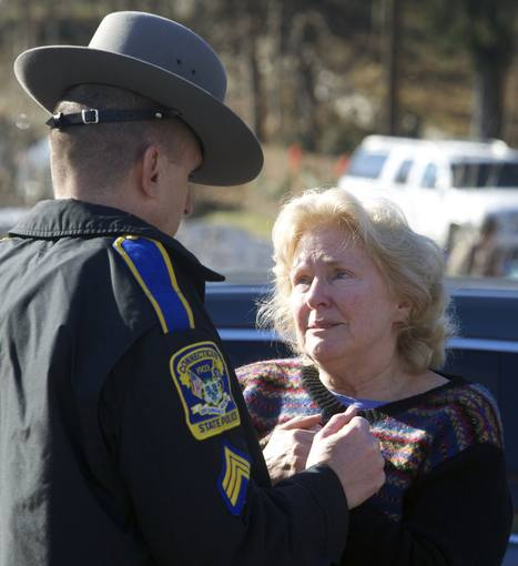 A woman speaks with a Connecticut State Trooper outside Sandy Hook Elementary School after a shooting in Newtown